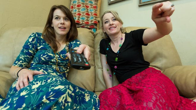 """Sisters Bailey Williams, 31, left, and Piper Gibson, 36, hang out watching television. Growing up, """"I think we got treated differently,"""" Gibson said. """"I got in trouble all the time and I got spanked all the time, whereas Bailey got a talking-to and she rarely got into the trouble that I got in."""""""