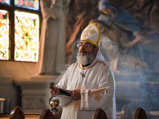 Father Girgis Ramandious carries the incense offering