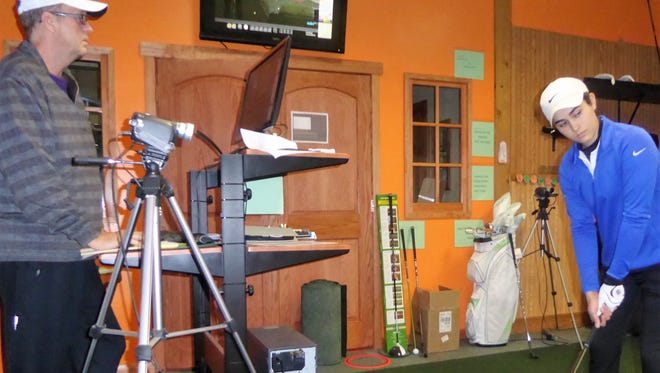 Golf Instructor Paul Mindel prepares to video Lorenza Martinez's golf swing during a winter practice session at Swing Time in Germantown.