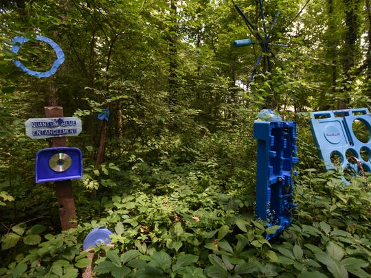 "Part of The Blue Loop installation in the wooded lot on Bath artist Robert Park's property, Thursday, July 5, 2018.  Park has been told by the township to clean up the ""junk,"" which he views as an art installation. He has a bachelor's degree in fine arts from Michigan State University. He also earned his teaching certificate there. He had a solo show at MSU in the fall of 2017."