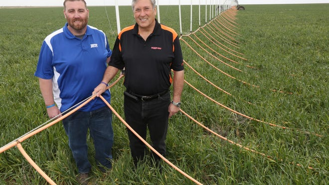 Monty and John Teeter, father and son, stand by their Dragon-Line system by Teeter Irrigation, of Ulysses, which they unveiled in March 2015. Dragon-Line is one of five finalists for the Governor's Exporter of the Year award.