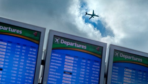 A plane takes off over departure boards at Hartsfield-Jackson