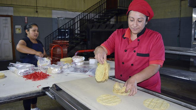 Erica Molina, right, and Judy Navarro, employees at La Mejor del Valle restaurant and grocery store in Farmersville, sort and package tortillas made and sold there or used in the restaurant every day.