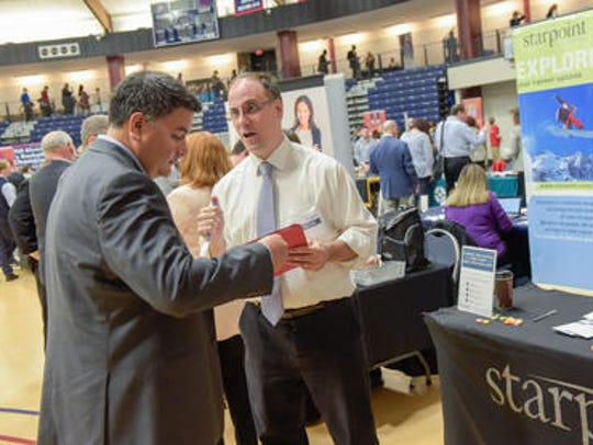 Employers talk to prospective workers at a career fair