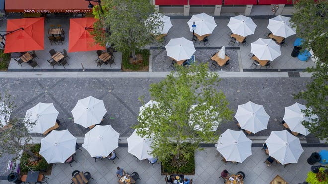 """Tables and umbrellas for patrons to use for the """"Dining on the Spot"""" initiative increasing outdoor seating on Clematis Street. It also allow the areas for restaurants to extend beyond traditional cafe seating onto streets, parking lots and alleys while following CDC guidelines for social distancing of six feet in West Palm Beach, Florida on May 19, 2020."""