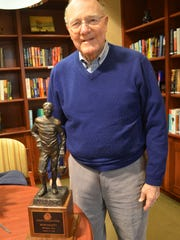Former University of Iowa Athletics Director Bump Elliott is pictured with his Rose Bowl Hall of Fame trophy. Elliott has played, coached and served as an administrator in the Rose Bowl seven times at the University of Michigan and UI.