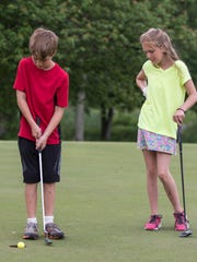 Harper Creek fourth-grader Nathan Norris taps his putt