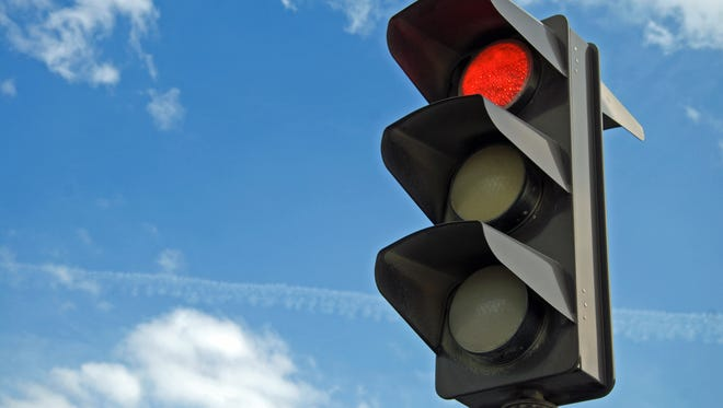 Red color on the traffic light with a beautiful blue sky in background.