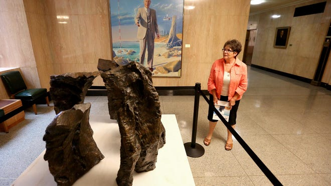 "Lorraine Dye, retired events programmer, discusses a bronze sculpture, ""Five Parts in Search of a Circle"" by Hilda Morris, during a tour of Oregon's State Capitol Art Collection. Henk Pander's ""Portrait of Governor Tom McCall"" is in the background."