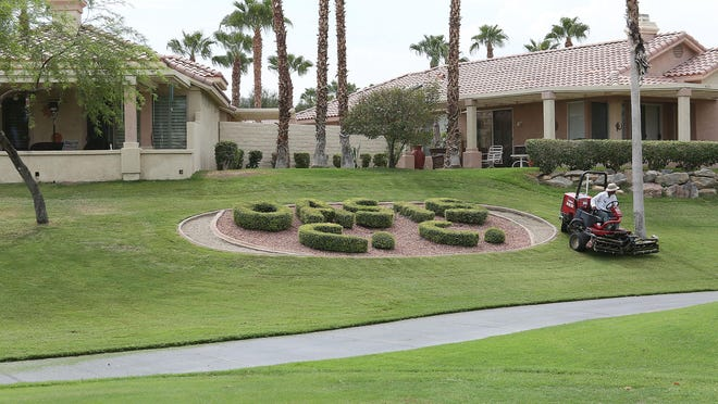 """A landscaper takes care of the lawn at Oasis Country Club in Palm Desert, Thursday, Sept. 10, 2015. """"Oasis C.C."""" is carved into several hedges on the property."""