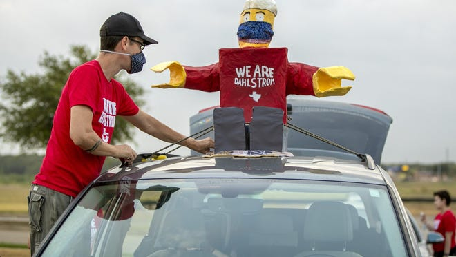 Dahlstrom Middle School engineering teacher Aaron Higdon decorates his car with a Lego man for a back-to-school parade Wednesday as the Hays school district prepares for its first virtual day of school next Tuesday.