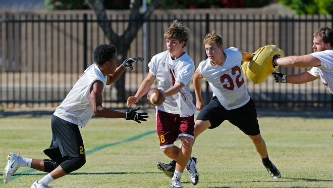 Phoenix Mountain Pointe's Bobby Manning hands off at practice Monday.