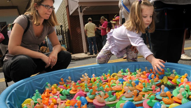 Caroline Healy, 4, of Gambrills, Md., picks a duck for a prize as her mom, Amy, looks on during the 16th annual Berlin Spring Celebration on Main Street in Berlin Saturday. Festivities included an Easter bonnet parade, cupcake eating contest, food, amusement rides and games.