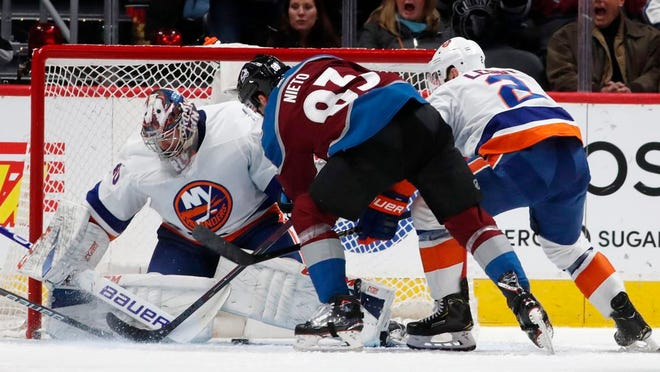 New York Islanders goaltender Semyon Varlamov, left, stops a shot by Colorado Avalanche left wing Matt Nieto as Islanderss defenseman Nick Leddy covers during the second period of an NHL hockey game Wednesday, Feb. 19, 2020, in Denver.