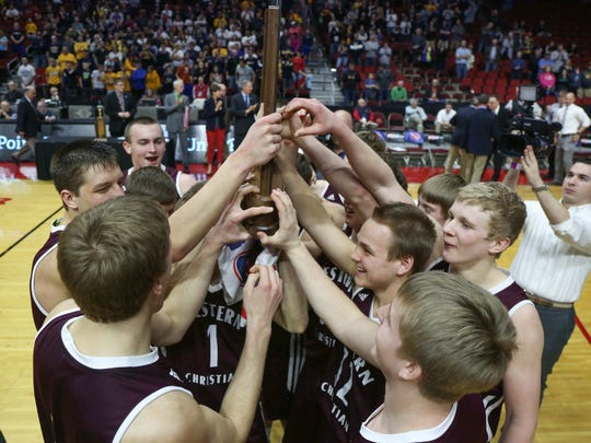 Members of the Western Christian boys basketball team celebrate after a state 2A championship win over Cascade on March 11, 2016, at Wells Fargo Arena in Des Moines.