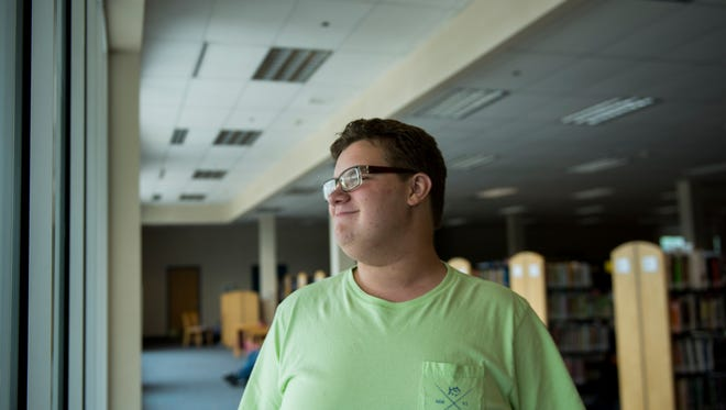 Christopher Miller, 15, poses for a portrait in one of his favorite places: Clarksville-Montgomery County Public Library. Miller and his brother Curtis Jr. are releasing their book in September on Captain Spectrum, a superhero who stops bullying.