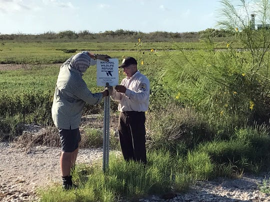 FlatsWorthy volunteer Ross Craft (left) and Santiago Muñoz of the Aransas National Wildlife Refuge post a boundary sign at the refuge.