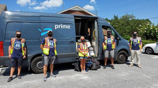 (L to R) Amazon team members Karl Nelson, Shawn Carbone, Amber Eslinger, Joshua Todd, Greg Miller marked the opening of the  Amazon delivery station in Port Wentworth recently by donating school supplies to Effingham County school district.