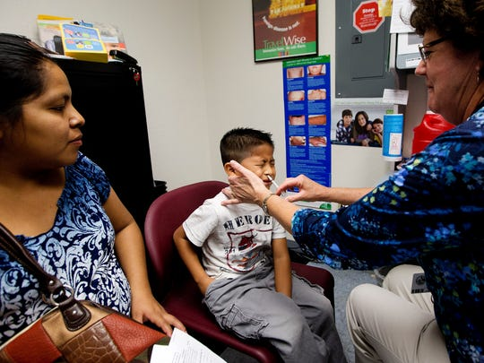 Luis Jimenez,7, receives a nasal spray flu vaccine Monday from R.N. Pat Freve at the state Health Department in Lee County. His mother, Eulalia Pedro, left, looks on.