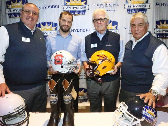 Ben Leeser, second from left, of Hyundai of El Paso, and John Folmer, Sun Bowl football committee chairman, hold helmets to North Carolina State and Arizona State, respectively, after the announcement that the two teams will play in the 2017 Hyundai Sun Bowl Game Dec. 29. At far left is Sun Bowl Association board president Bill Coon and at far right is Bernie Olivas, Sun Bowl Executive Director.