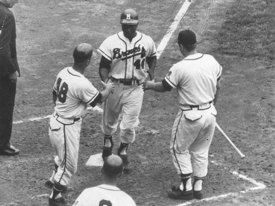 Milwaukee Braves slugger Hank Aaron crosses the plate during a game against the St. Louis Cardinals.