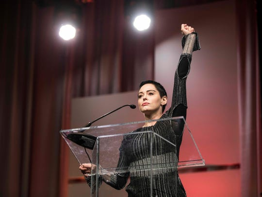 Rose McGowan raises her fist as she speaks during during the Women's Convention in Detroit on Oct. 27, 2017.