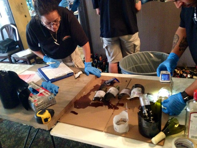 Restoration workers with Servpro of Central Brevard take inventory of broken wine bottles Thursday in the Black Tulip dining room.