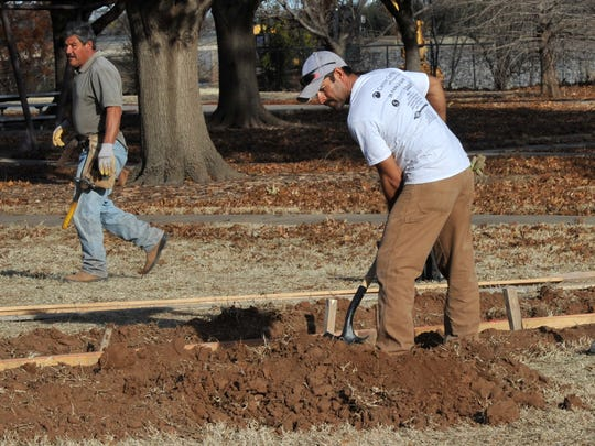 Construction crew works on a news playground in Hamilton Park. The park is a project of the Wichita County Medical Alliance.