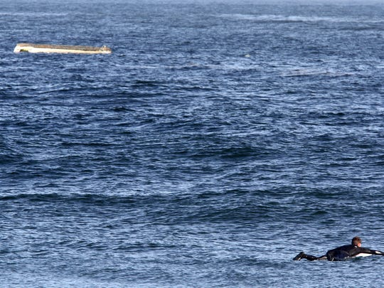 A surfer paddles out close to a capsized boat close