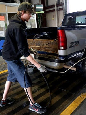This file photo from April 6, 2015, shows Benjamin Raper, the assistant manager at the Tennessee Vehicle Inspection Center in Murfreesboro, removing the exhaust probe from the tailpipe of a truck.