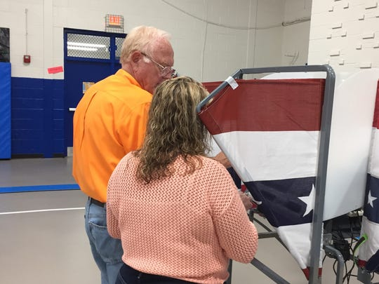 Lori Edwards, right, gets ready to vote at Lakeview Elementary School in Wilson County, Nov. 8, 2016. Poll worker Joe Fitzgerald, left, provides instructions.