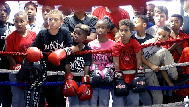 Young boxers at SIMS Boxing Gym on East 10th Street wait to receive their new boxing gloves Wednesday, Sept. 6, 2017. Billy Vaughan, of Title Boxing Clubs, organized a donation drive and  gave 75 pairs of gloves to the kids at SIMS Boxing Gym.