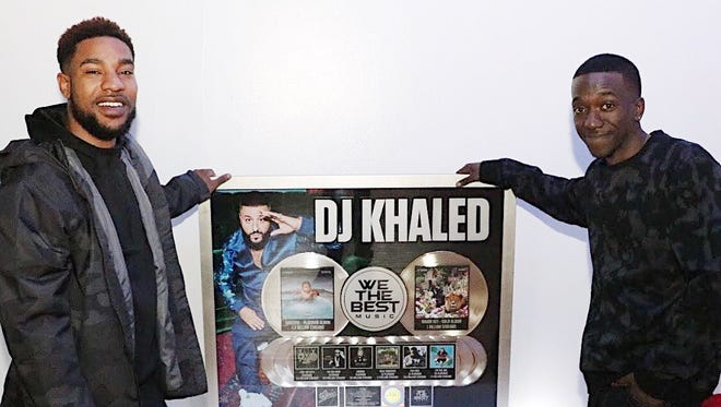 """Freeman McGaw (left) who goes by DJ Freeez on air, and his mentor, Donovon """"Kent"""" McKnight, who goes by DJ Dark Kent, with the Epic Records plaque awarded to McGaw. DJ Khaled is a famous DJ and record producer signed to Epic Records."""