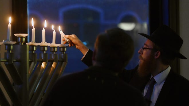 Rabbi Mendel Alperowitz, co-director of Chabad Jewish Center of South Dakota, and the only rabbi in the state, lights the Menorah during a community-wide Chaunkah celebration at the Washington Pavilion on Wed., Dec. 28, 2016.