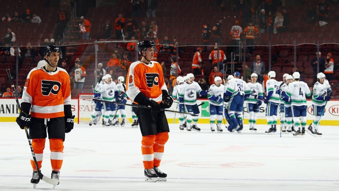 Taylor Leier #20 and Travis Sanheim #6 of the Philadelphia Flyers leave the ice following a 5-2 loss to the Vancouver Canucks.