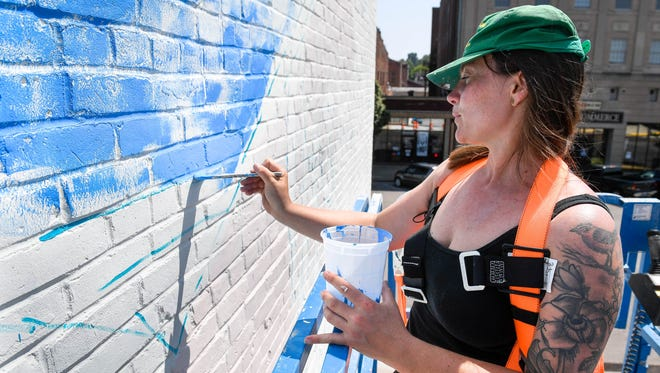 "Professional artist and Wisconsin native Leah Tumerman begins work on her mural, painted on a private building to provide the backdrop for Henderson's newest park, a ""pocket park"" on Second Street called The Perch Thursday, July 12, 2018."