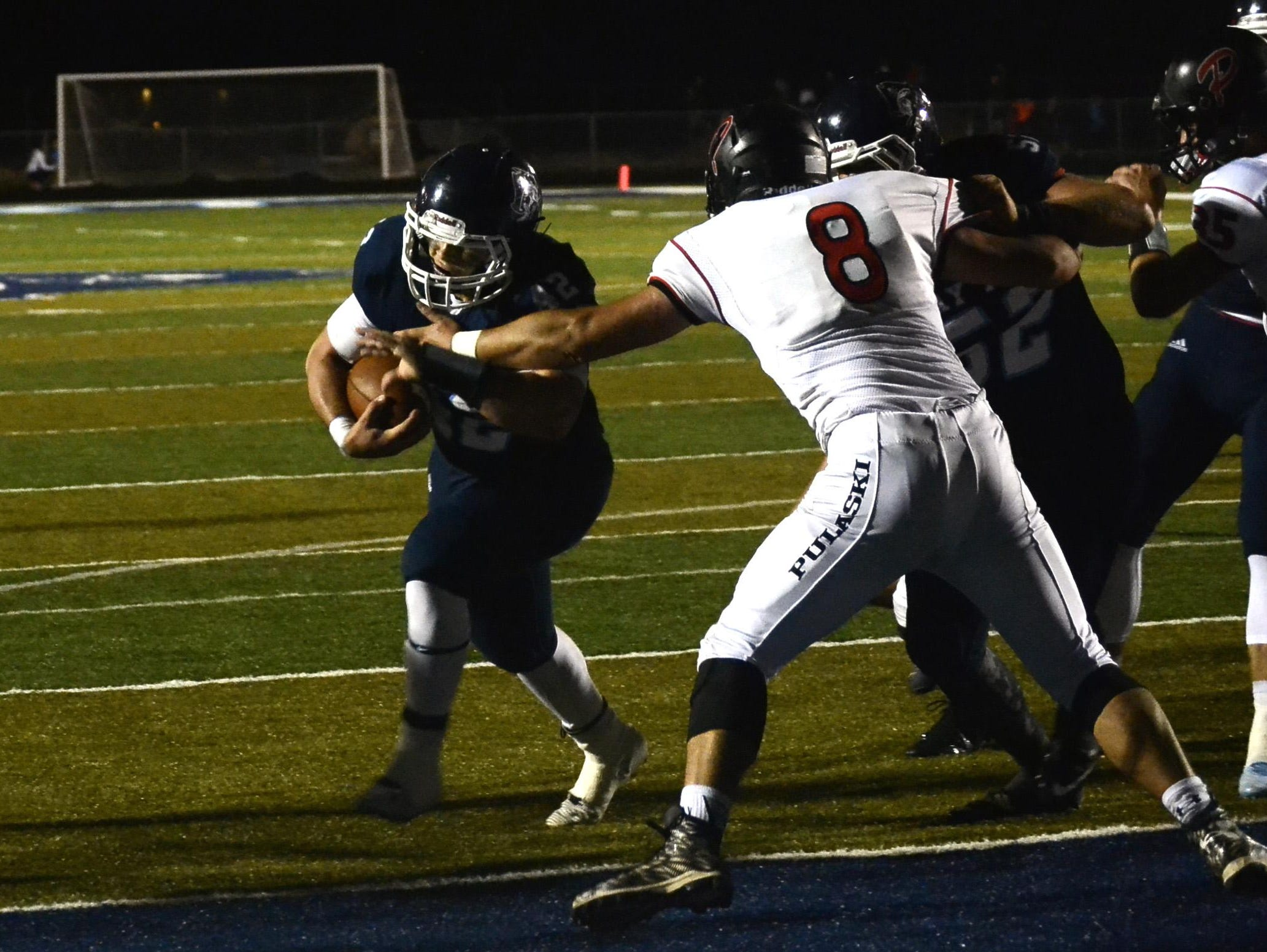 Bay Port's Evan Bindas rushes past Pulaski's Michael Woodworth and into the endzone in Friday's FRCC game, won by the host Pirates 42-14.
