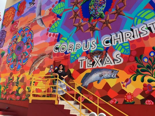 Muralist Sandra Gonzalez is the artist who created the Caller-Times mural titled 'Endless Sunset: The Colors of Our City.' The project involved months of work by Gonzalez, community members and local artists to be complete.
