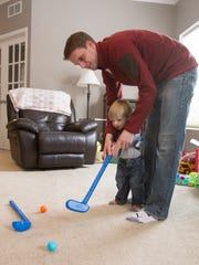 Nicholas Alimpich helps his 17-month-old son, Robert, with his golf swing Thursday, Mar. 8, 2018 in their Brighton Township home. Robert was conceived by in-vitro fertilization, and the family is expecting their second child through the same method.