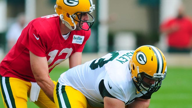 Green Bay Packers center Corye Linsley works with quarterback Aaron Rodgers during training camp practice at Ray Nitschke Field, Monday, August 25, 2014.