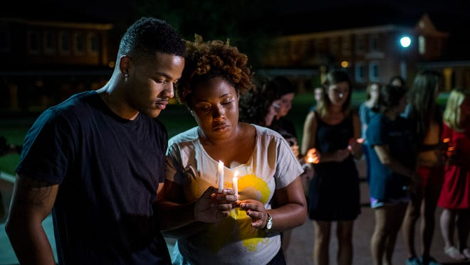 Sheldon Gilton, a UL business student, Brea Butler, a psychology student, pray during a candlelight vigil for the Grand 16 Theatre shooting victims at the University of Louisiana at Lafayette in Lafayette, La., Friday, July 24, 2015. Two victims were killed with an additional nine wounded in a shooting at the movie theater on Thursday evening.