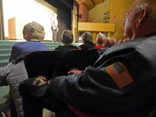 A man in the audience rests a Coast Guard hat on his