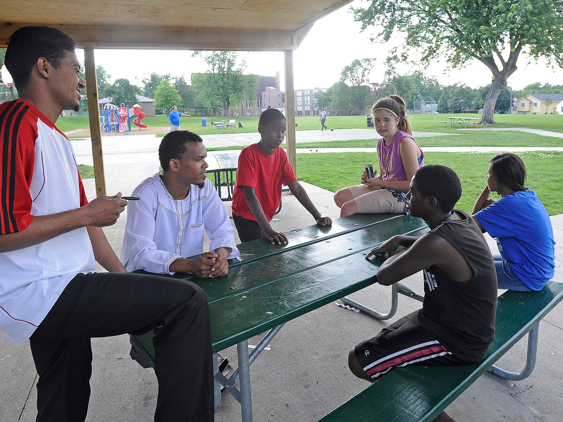 Ramzy Omarr and Sadik Muhammad, Mohamed, Alyssa Krush, Ashmita Biswa and Abel Balih hang out at Meldrum Park in the Whittier neighborhood in Sioux Falls, S.D., Thursday, July 9, 2015.
