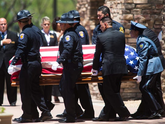 The casket of Officer Jair Cabrera is carried to a hearse outside Christ's Church of the Valley in Peoria after a memorial service on  May 30, 2014.