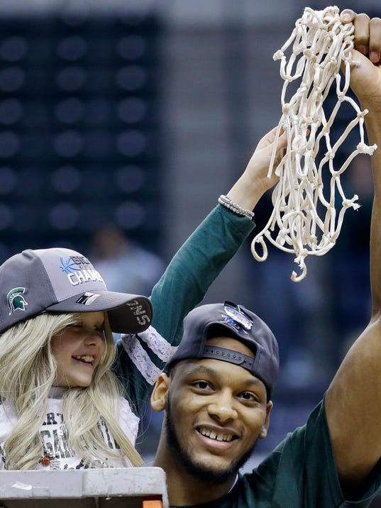 FILE - In this March 16, 2014 file photo, Michigan State forward Adreian Payne, right, hoists the net with Lacey Holsworth, after Michigan State defeated Michigan 69-55 in an NCAA college basketball game in the championship of the Big Ten Conference tournament in Indianapolis. Mourners are to gather tonight at Michigan State's Breslin Center to celebrate the life and legacy of Lacey Holsworth, an 8-year-old girl, who died last week because of cancer.(AP Photo/Michael Conroy, File)