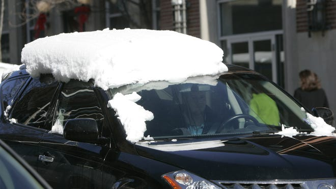 A vehicle with a snow-capped roof travels along Broadway in Nyack in 2010. Flying chunks of ice can pose a hazard to other vehicles, but some drivers