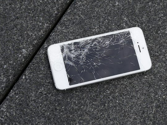 Top: The screen of an Apple iPhone cracked after being dropped by a DropBot. In recent tests, the latest iPhones and the Galaxy Note 5 survived 10 drops each from six feet.