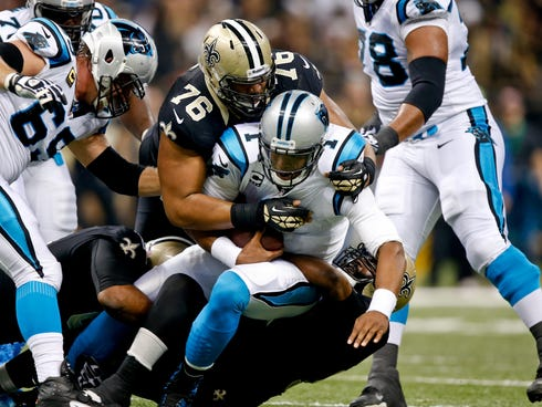 Dec 8, 2013; New Orleans, LA, USA; Carolina Panthers quarterback Cam Newton (1) is sacked by New Orleans Saints defensive end Akiem Hicks (76) and outside linebacker Junior Galette (93) and defensive end Cameron Jordan (94) during the first quarter o