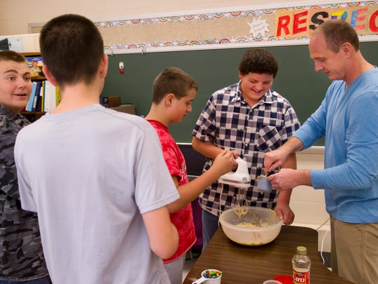 Nicholas Berry, right, adds some peanut butter to the monster cookie mixture his students, from left, Reily Whitler, 14, Alex Bare, 13, Ronald Lindauer, 12, and Adam Moye, 12, were getting ready to bake in their North Posey High School classroom recently.
