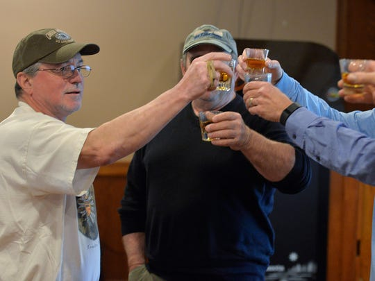 Peg 'n Keg tournament organizer John Forsythe, left, joins friends in a toast for close friend Dan Whalen who died two months after last year's cribbage tournament.